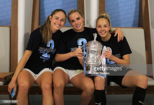 Janine Beckie, Alex Greenwood and Ellie Roebuck of Manchester City celebrate in the dressing room with the Vitality Women's FA Cup Trophy following...