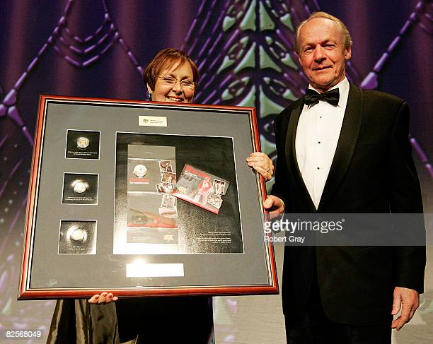 Janine Murphy of the Royal Australian Mint presents John Bradman with a Montage of a commemorative coin during the Sir Donald Bradman Centenary...
