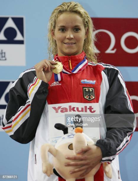 Janine Pietsch of Germany shows off her gold medal after winning the Women's 100m backstroke final during day two of the FINA World Swimming...