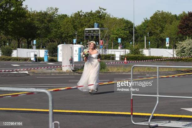 Janine Scholz, dressed in a cream white dress runs across the empty car park prior to her marrigare to Philip Scholz during the first ever wedding...