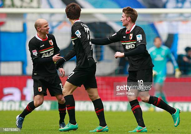 Jan-Ingwer Callsen-Bracker of Augsburg celebrates with his team mates after scoring his team's first goal during the Bundesliga match between...