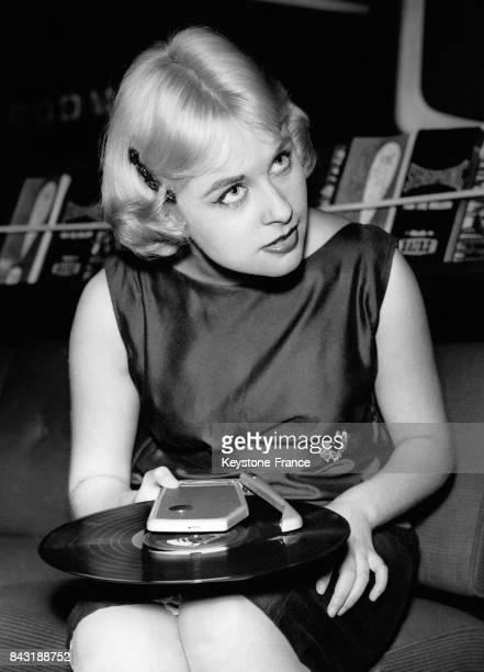 Janis James, une jeune femme blonde, fait la démonstration du 'Wondergram', le plus petit gramophone automatique du monde, au Radio Show le 26 août...
