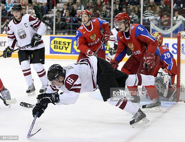 Janis Ozolins of Latvia looses his footing as he passes the puck while Vasili Tokranov of Russia looks on at the Civic Centre on December 26, 2008 in...