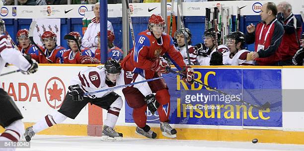 Janis Ozolins of Latvia tries to slow down Sergei Andronov of Russia for the loose puck at the Civic Centre on December 26, 2008 in Ottawa, Ontario,...
