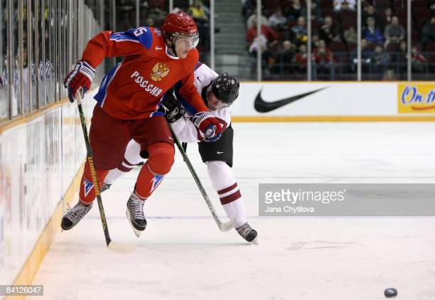 Janis Smits of Latvia chases Evgeni Grachev of Russia as he carries the puck at the Civic Centre on December 26, 2008 in Ottawa, Ontario, Canada.