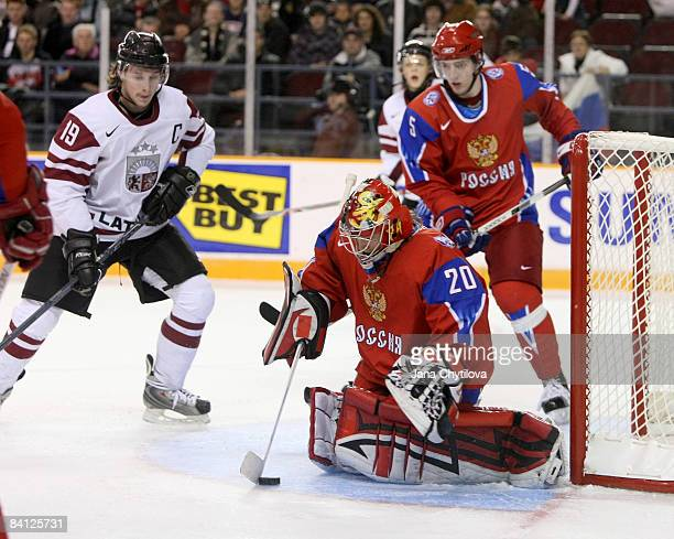 Janis Straupe of Latvia looks on as Danila Alistratov of Russia makes a save and teammate Maxim Goncharov of Russia also looks on at the Civic Centre...