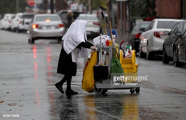 A janitor ducks under a towel while walking across the street in downtown Riverside as the second major El Niño storm of the season brings heavy...