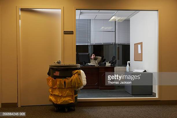 Janitor in office late at night, sitting with feet up at desk