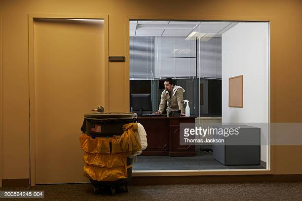 Janitor in office late at night, working on CEO's computer