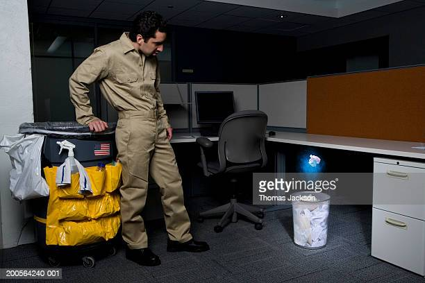 Janitor in office, surprised by glowing paper rising from wastebasket