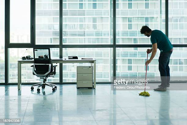 janitor mopping empty office - janitor stock photos and pictures