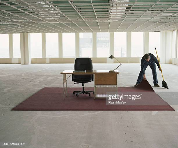 Janitor sweeping dust under rug in office space
