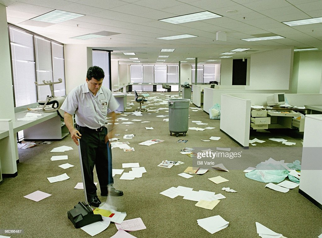 Janitor Sweeping Papers From Floor In Messy Office Stock Photo