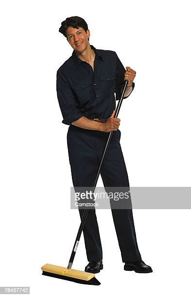 Janitor with push broom