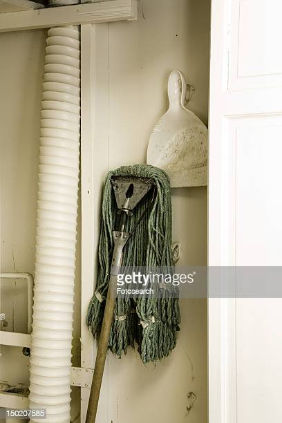 janitorial mop and dustpan in white closet - janitorial supplies stock photos and pictures