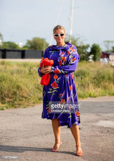 Janka Polliani is seen wearing purple dress with floral print, red bag outside Cecilie Bahnsen during Copenhagen Fashion Week Spring/Summer 2020 on...