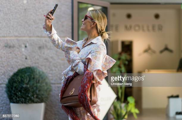 Janka Polliani taking a photo wearing a dress brown Mulberry bag outside Moods of Norway on August 22 2017 in Oslo Norway