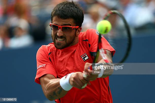 Janko Tipsarevic of Serbia returns a shot against David Ferrer of Spain during their men's singles quarterfinal match on Day Eleven of the 2012 US...