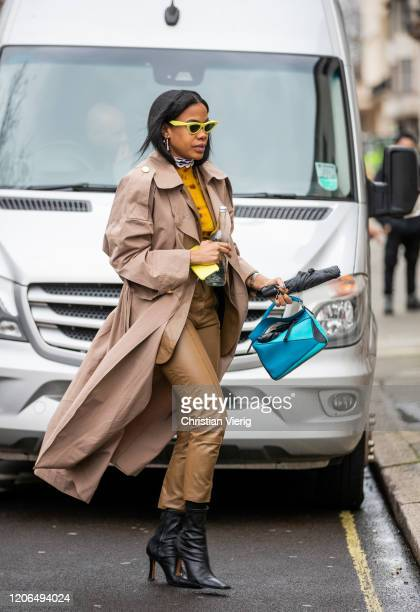 Jan-Michael Quammie is seen wearing brown trench coat, camel pants and jacket, black boots, blue Loewe bag outside Petar Petrov during London Fashion...