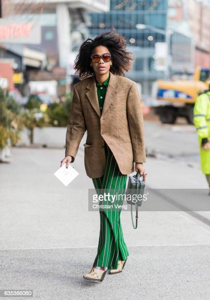 JanMichael Quammie wearing a striped green suit brown blazer outside Tory Burch on February 14 2017 in New York City