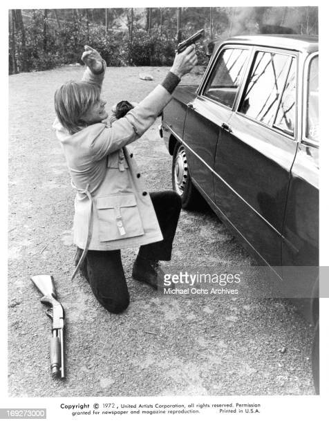 JanMichael Vincent aiming pistol over car in a scene from the film 'The Mechanic' 1972