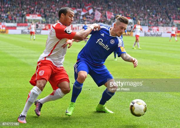 Jann George of Jahn Regensburg challenges Steven Lewerenz of Holstein Kiel during the 3 Liga match between Jahn Regensburg and Holstein Kiel on April...