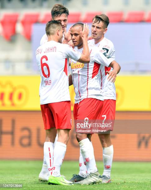 Jann George of Regensburg celebrates his team's second goal with teammates Benedikt Saller and Max Besuschkow during the Second Bundesliga match...