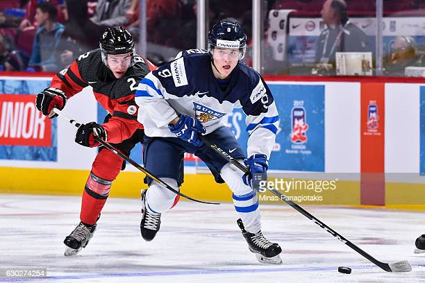 Janne Kuokkanen of Team Finland skates the puck against Jake Bean of Team Canada during the IIHF exhibition game at the Bell Centre on December 19...