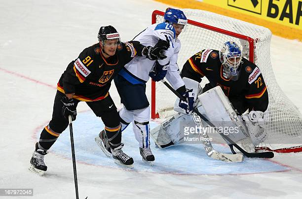 Janne Pesonen of Finland and Moritz Mueller of Germany battle for position during the IIHF World Championship group H match between Finland and...