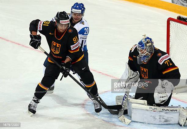 Janne Pesonen of Finland and Moritz Mueller of Germany battle for the puck during the IIHF World Championship group H match between Finland and...