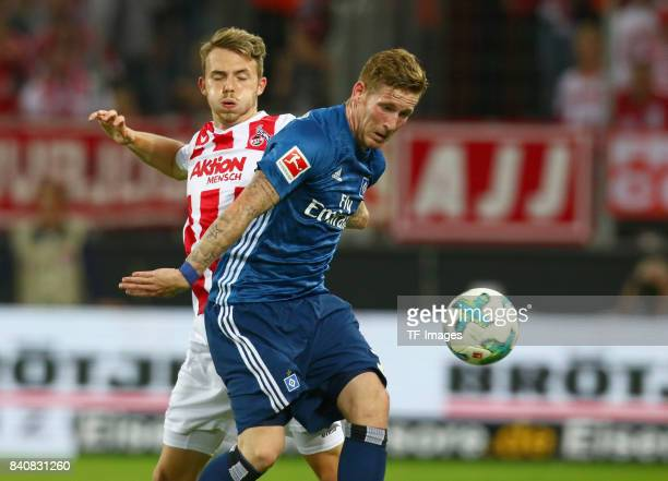 Jannes Horn of Koeln and Andre Hahn of Hamburg battle for the ball during the Bundesliga match between 1 FC Koeln and Hamburger SV at...