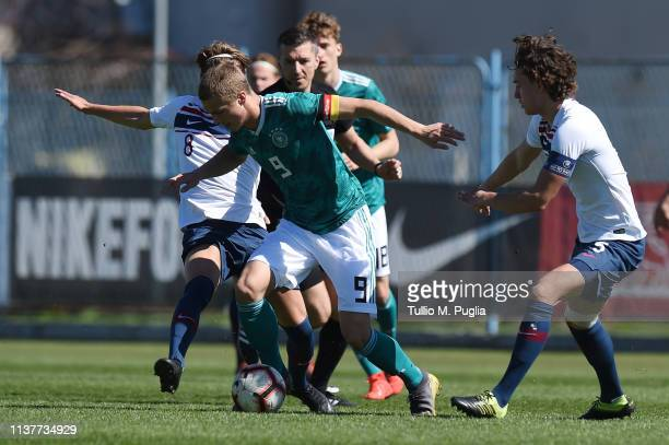 JannFiete Arp of Germany is challenged by Mikael Ugland and Colin Rosler of Norway during the UEFA Elite Round match between Norway U19 and Germany...