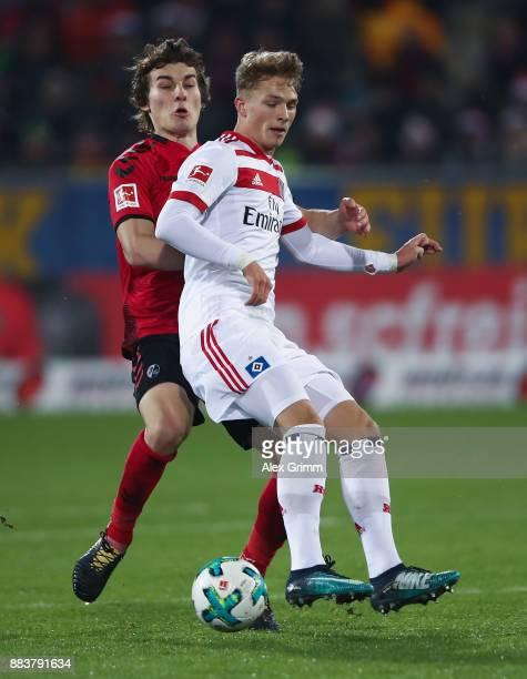 JannFiete Arp of Hamburg is challenged by Caglar Souyuencue of Freiburg during the Bundesliga match between SportClub Freiburg and Hamburger SV at...