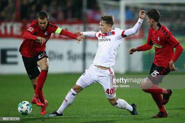 JannFiete Arp of Hamburg is challenged by Julian Schuster and Pascal Stenzel of Freiburg during the Bundesliga match between SportClub Freiburg and...
