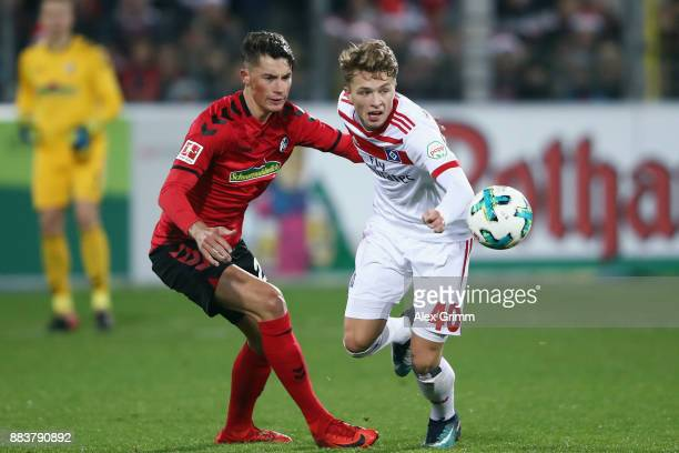 JannFiete Arp of Hamburg is challenged by Robin Koch of Freiburg during the Bundesliga match between SportClub Freiburg and Hamburger SV at...
