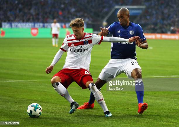 JannFiete Arp of Hamburger SV is challenged by Naldo of Schalke 04 during the Bundesliga match between FC Schalke 04 and Hamburger SV at VeltinsArena...