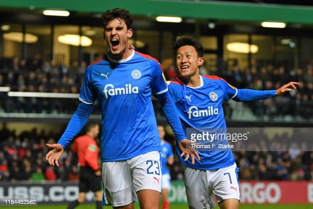 Janni Serra and Jaesung Lee of Kiel celebrate their teams first goal during the DFB Cup second round match between SC Verl and Holstein Kiel at...