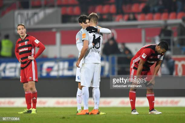 Janni Serra and Lukas Hinterseer of Bochum hug at the final whistle as Tobias Schroeck and Marvin Matip of Ingolstadt look on during the Second...