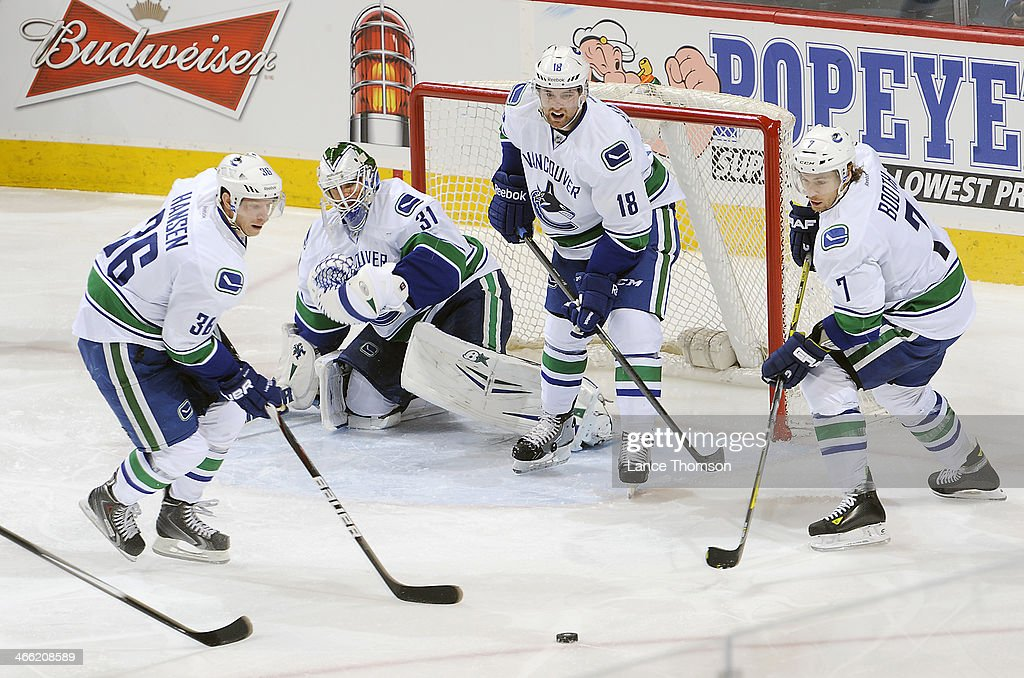 Jannik Hansen #36, goaltender Eddie Lack #31, Ryan Stanton #18 and David Booth #7 of the Vancouver Canucks eye the puck them during second period action against the Winnipeg Jets at the MTS Centre on January 31, 2014 in Winnipeg, Manitoba, Canada.