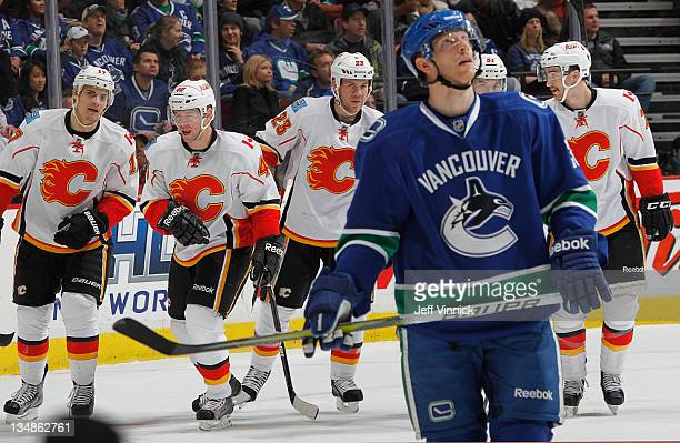 Jannik Hansen of the Vancouver Canucks checks the replay while Rene Bourque goal scorer Alex Tanguay Scott Hannan Roman Horak and TJ Brodie of the...