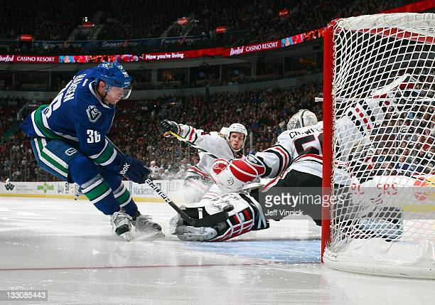 Jannik Hansen of the Vancouver Canucks directs the puck behind behind Corey Crawford of the Chicago Blackhawks for a goal during their NHL game at...