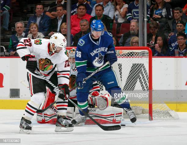 Jannik Hansen of the Vancouver Canucks redirects the puck for a goal while being checked by Johnny Oduya of the Chicago Blackhawks during their NHL...