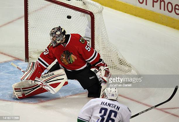 Jannik Hansen of the Vancouver Canucks scores a goal against Corey Crawford of the Chicago Blackhawks in the first period at the United Center on...