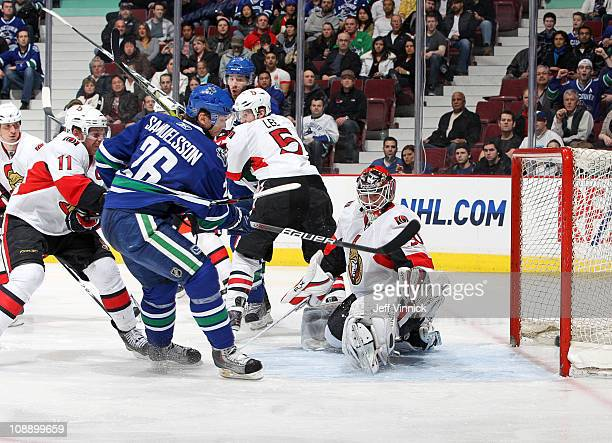 Jannik Hansen of the Vancouver Canucks scores on Brian Elliott of the Ottawa Senators while Daniel Alfredsson of the Ottawa Senators and Ryan Kesler...