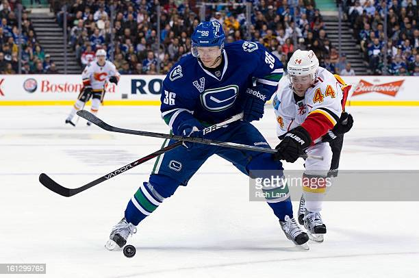 Jannik Hansen of the Vancouver Canucks tries to fight off the check of Chris Butler of the Calgary Flames during the second period in NHL action on...
