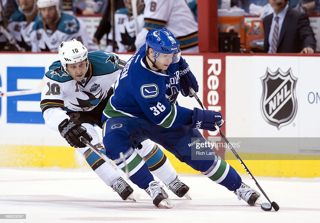 Jannik Hansen #36 of the Vancouver Canucks tries to protect the puck while being checked by Andrew Desjardins #10 of the San Jose Sharks during Game One of the Western Conference Quarterfinals of the 2013 NHL Stanley Cup Playoffs, May 01, 2013 at Rogers Arena in Vancouver, British Columbia, Canada.