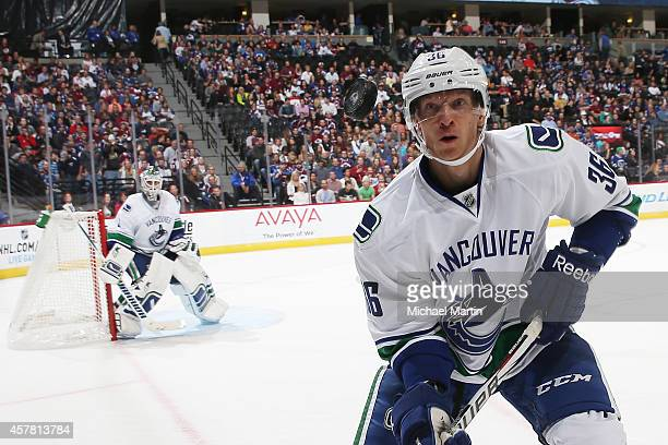 Jannik Hansen of the Vancouver Canucks watches the puck as goaltender Eddie Lack looks on against the Colorado Avalanche at the Pepsi Center on...