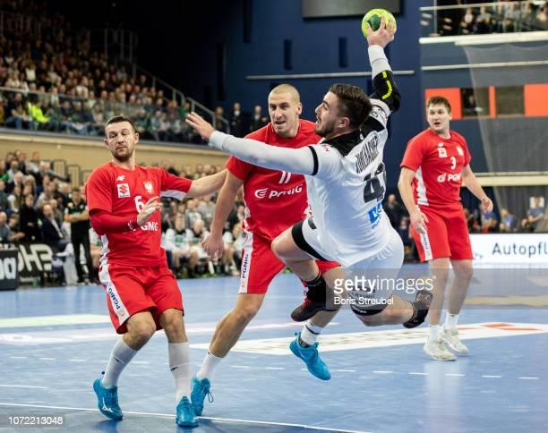 Jannik Kohlbacher of Germany in action with Przemyslaw Krajweski and Pawel Krupa of Poland during the international friendly handball match between...