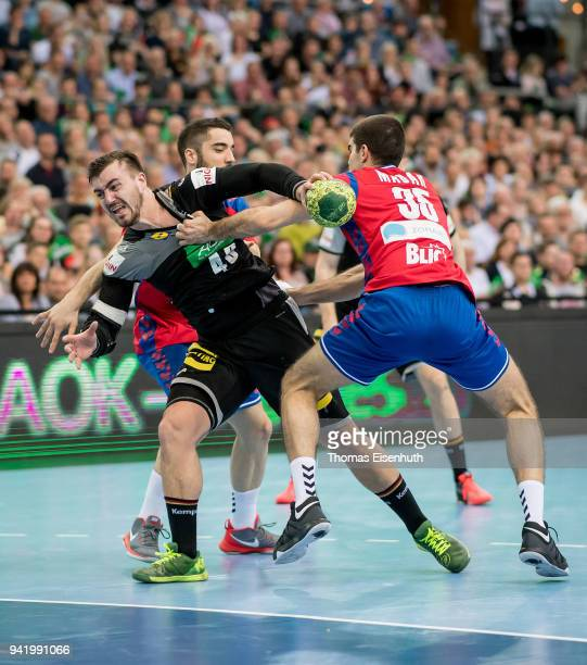 Jannik Kohlbacher of Germany is challenged by Andrija Madar and Janja Vojvodic of Serbia during the handball international friendly match between...