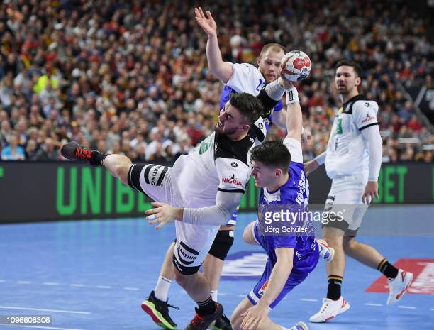 Jannik Kohlbacher of Germany is challenged by Elvar Orn Jonsson of Iceland during the 26th IHF Men's World Championship group 1 match between Germany...